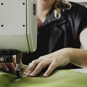 Artisane en train de coudre à la machine des morceaux de cuir vert