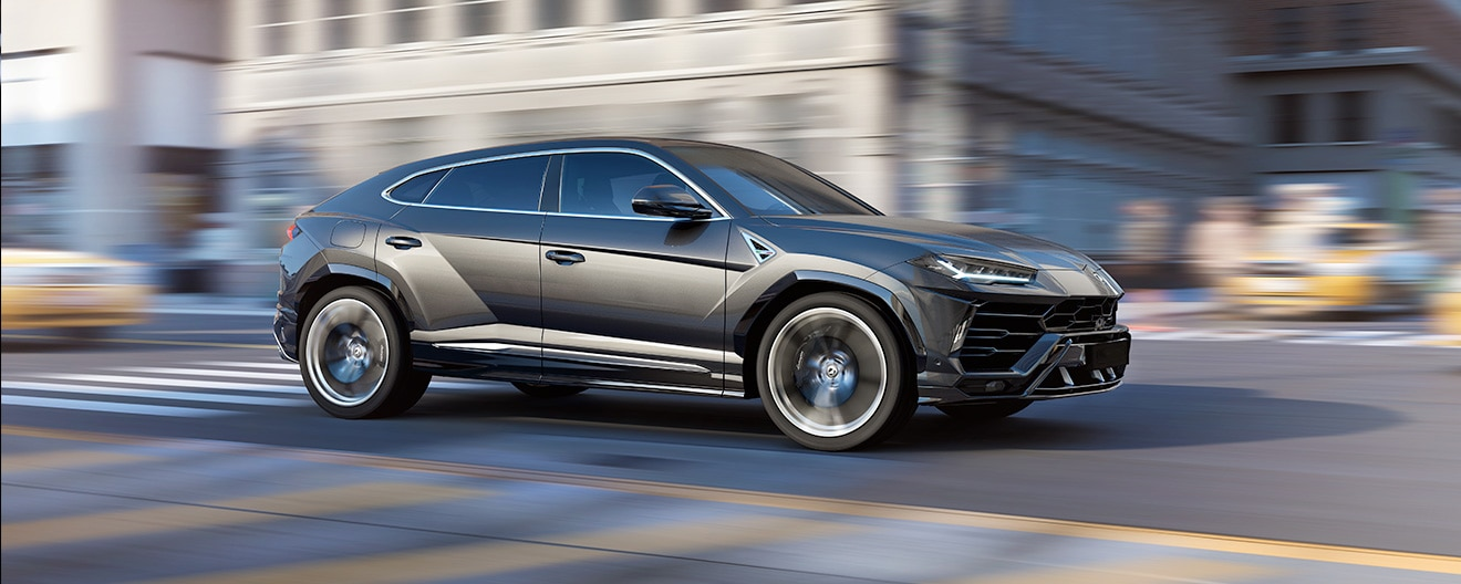 A coal gray Urus, seen from the side, as it travels along a city street