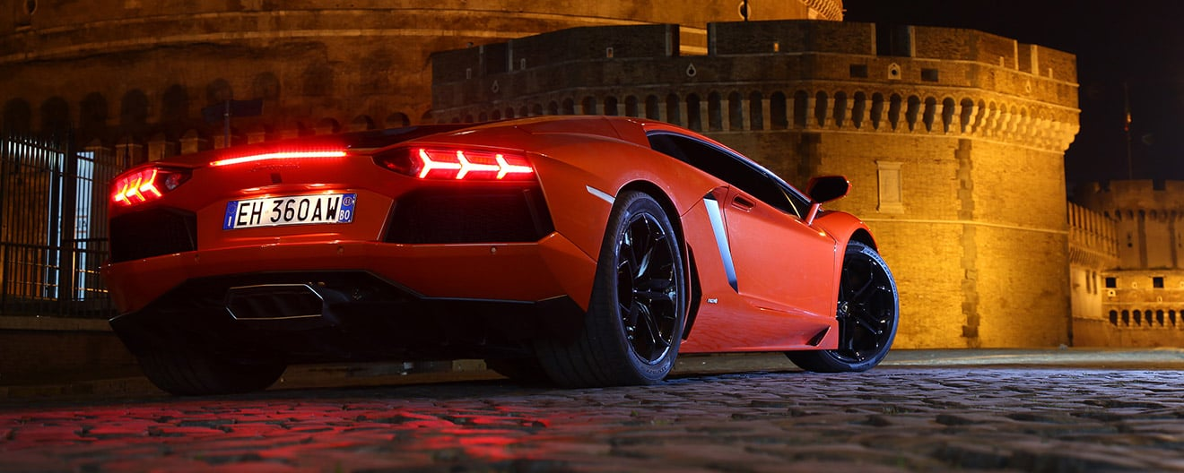 Night view of the rear end of a red Lamborghini Aventador Coupé with its taillights on, parked before an ancient castle.