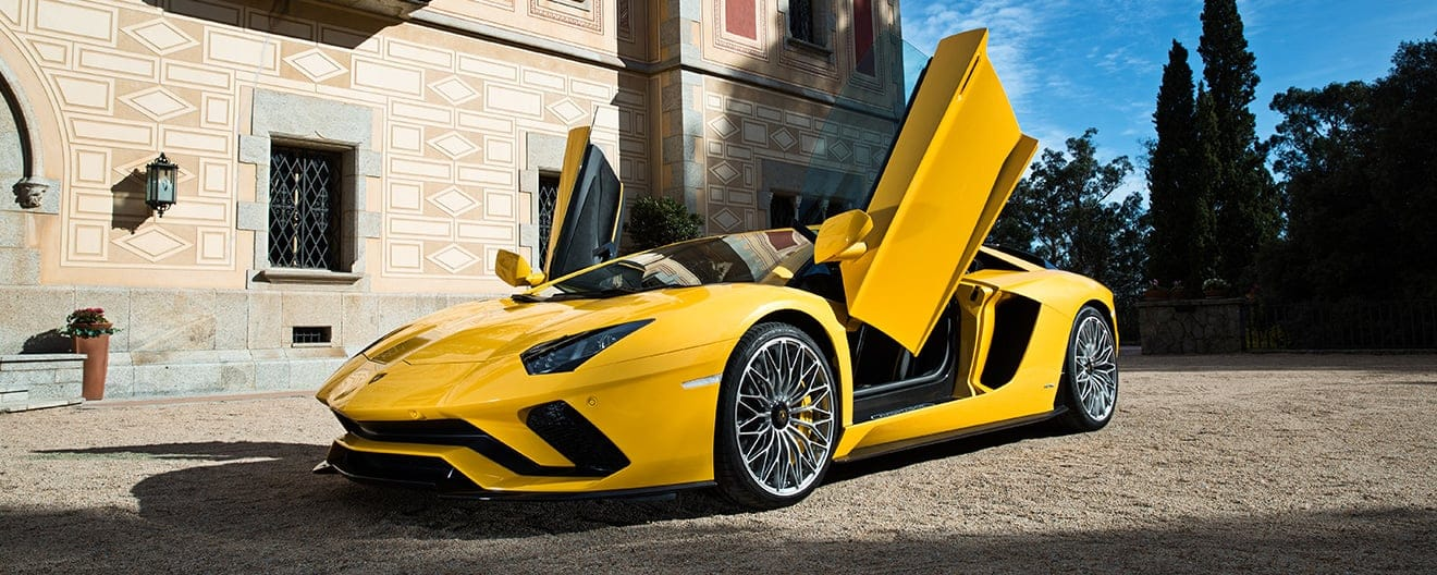 An angular front of a yellow Lamborghini Aventador S Coupé with vertical doors open.