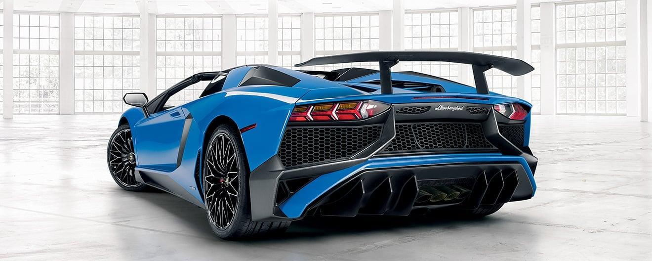 Image avec vue de trois quarts de l'arrière d'une Lamborghini Aventador SV Roadster bleue, dans un espace intérieur clair bordé de murs vitrés.