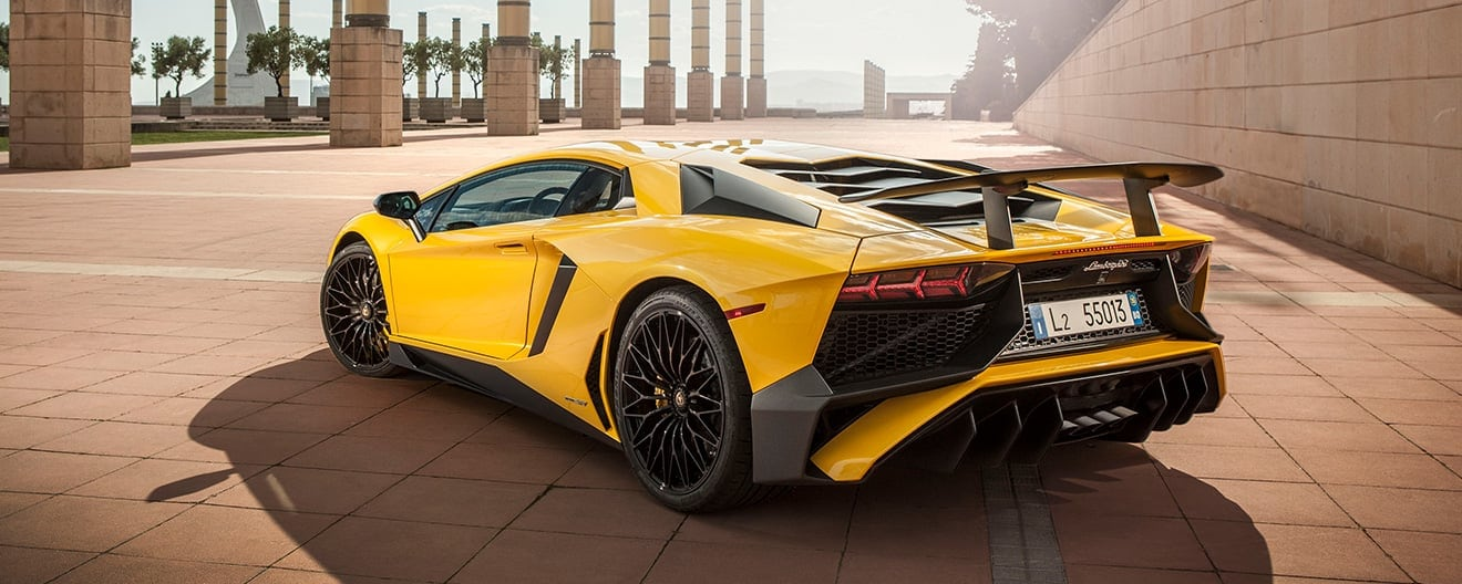 Rear three-quarter view of a yellow Lamborghini Aventador SV Coupé on a scenic terrace.