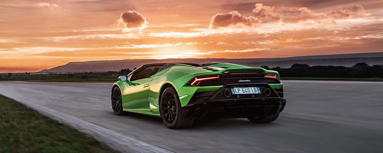 Huracán EVO Spyder зеленого цвета Verde Selvans стоит на дороге на фоне заката