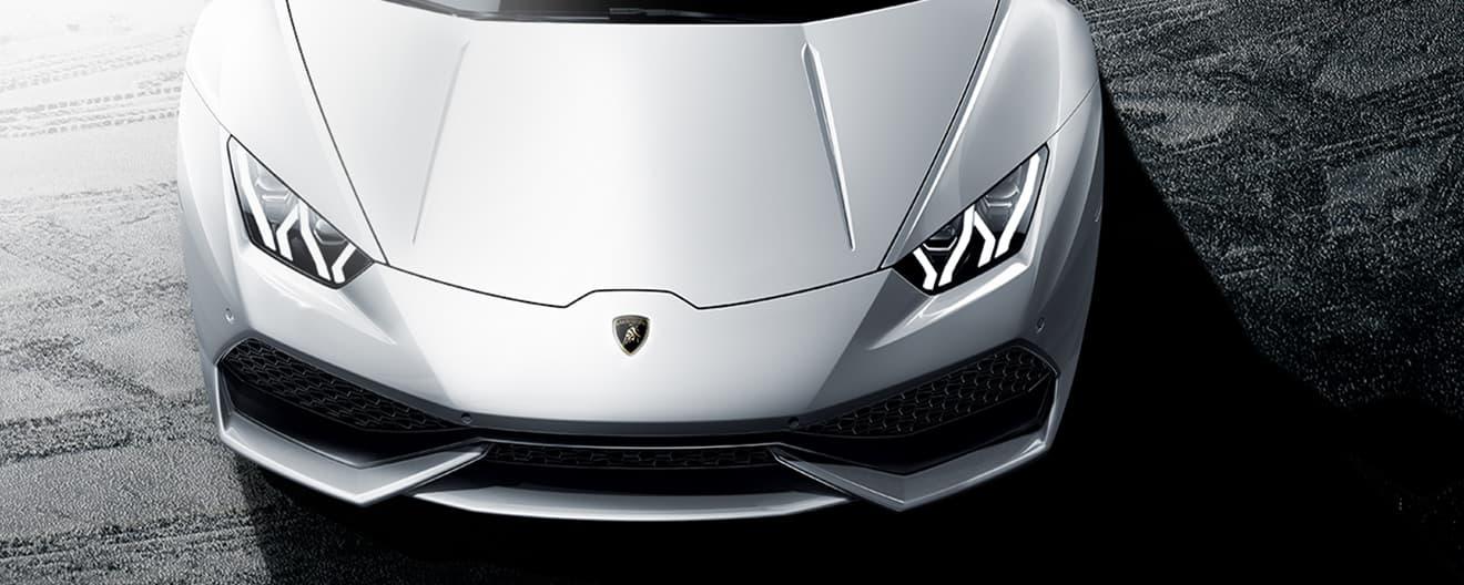 L'image montre au premier plan une Lamborghini Huracán Coupé blanche prise de dessus, dont on voit le capot et un phare.