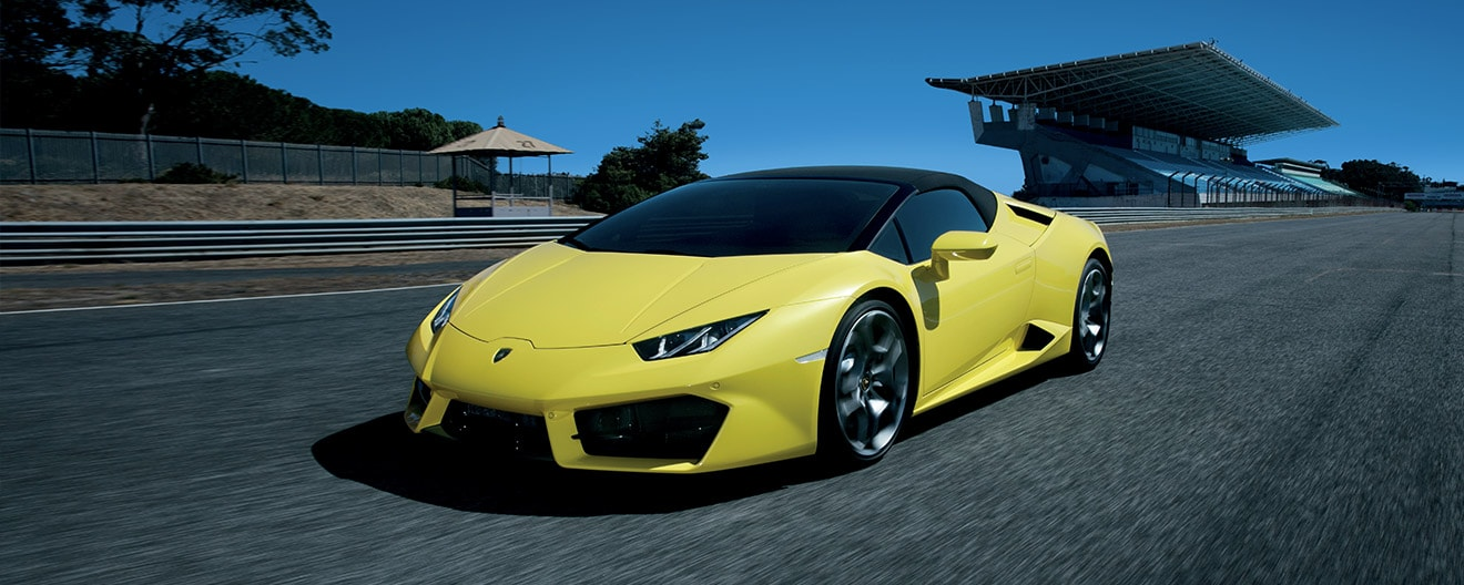 Three-quarter view of a yellow Huracán RWD Spyder at the track with black roof closed.