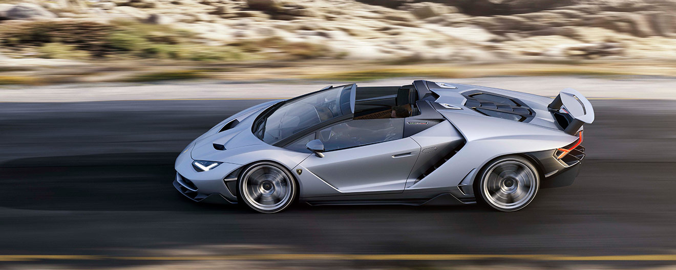 The picture shows the profile of a grey Lamborghini One Off Centenario Roadster racing along a road.